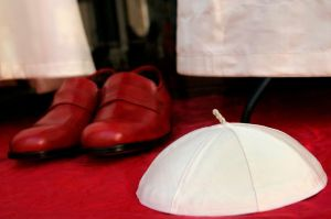 File picture of Papal white skull cap and burgundy shoes displayed in the Gammarelli's tailor shop window in Rome